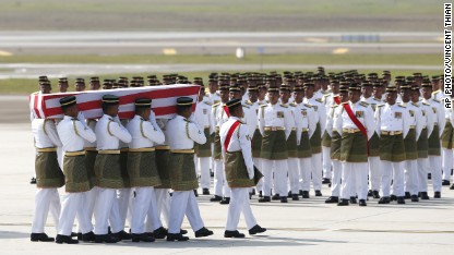 Malaysia Army soldiers carry one of the bodies of the downed MH17 flight on the arrival at Kuala Lumpur International Airport in Sepang, Malaysia, Friday, Aug. 22, 2014. The bodies of 20 victims' of the ill-fated Malaysia Airlines flight that was shot down over eastern Ukraine last month, returned home from Amsterdam on Friday. (AP Photo/Vincent Thian)