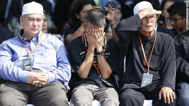 A family member covered his face with his hands as other family members watched Malaysian Army soldiers carry coffins from the plane.
