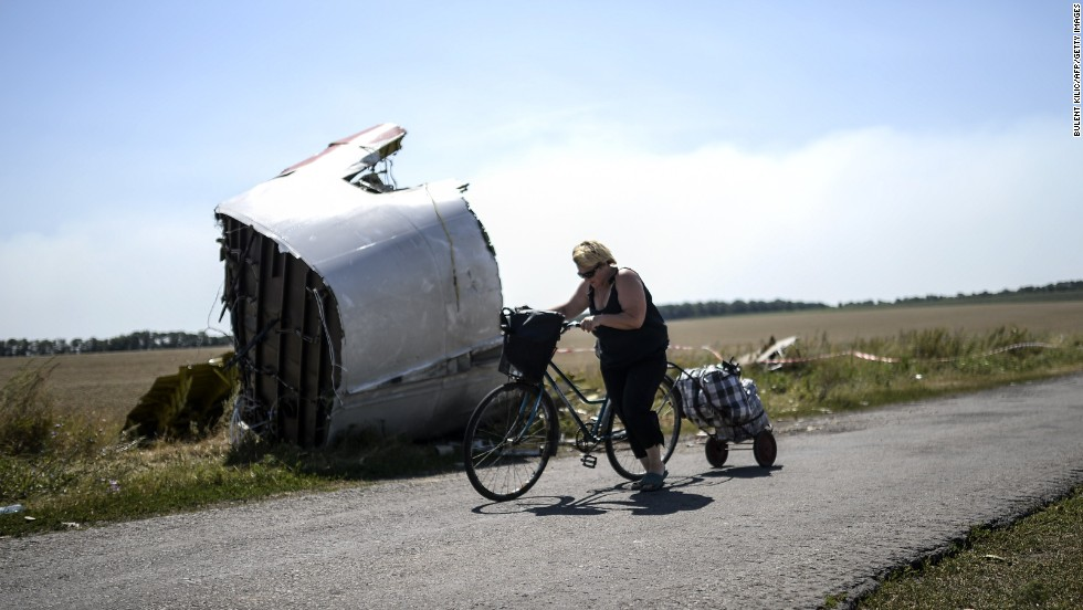 Malaysia Airlines Flight 17 crashed in mid-July in eastern Ukraine. Here, a woman walks with her bicycle near the crash site on Saturday, August 2.