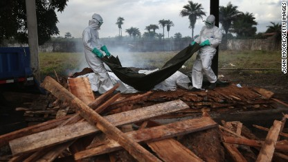 A burial team from the Liberian Ministry of Health unloads the bodies of Ebola victims onto a funeral pyre at a crematorium on August 22 in Marshall, Liberia.