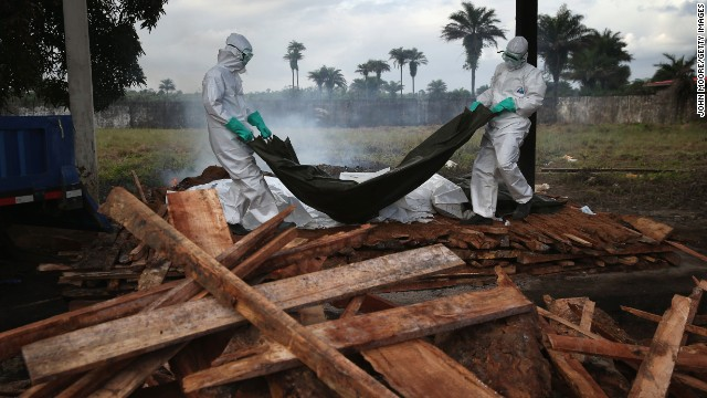 A burial team from the Liberian Ministry of Health unloads the bodies of Ebola victims onto a funeral pyre at a crematorium on Friday, August 22, in Marshall, Liberia.