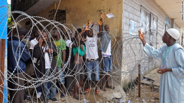 A humanitarian group worker, right, throws water in a small bag to West Point residents behind the fence of a holding area on August 22. Residents of the quarantined Monrovia slum were waiting for a second consignment of food from the Liberian government.