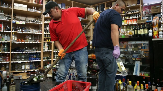 Eddie Villa, left, and Jesus Villa clean up broken bottles at Van's Liquors August 24 in Napa.