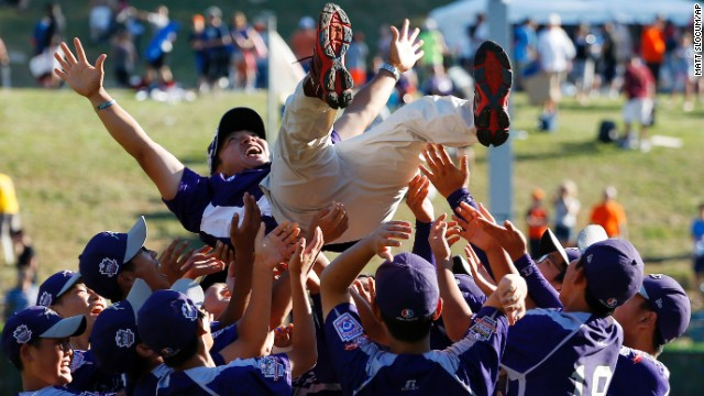 South Korean players hold coach Sang Hoon-hwang after winning the championship baseball game against Chicago at the Little League World Series in South Williamsport, Pennsylvania, on Sunday, August 24. South Korea won 8-4.