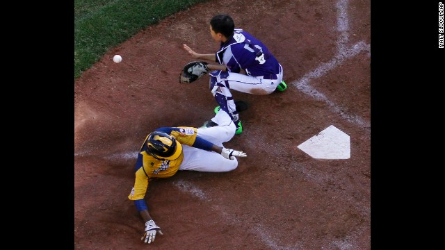 Chicago's Trey Hondras, in yellow, scores past South Korea's Sang Hoon-han on a two-run double by Darion Radcliff during the sixth inning on August 24.