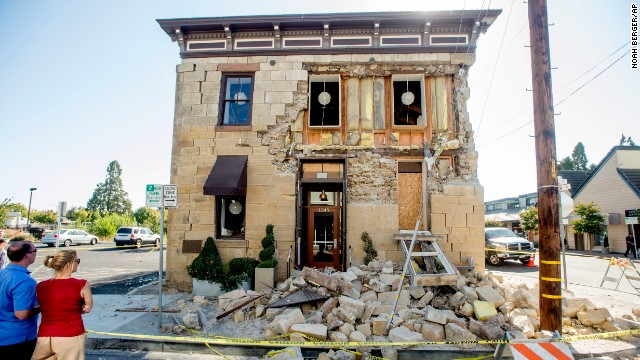 Pedestrians stop to examine a crumbling facade at the Vintner's Collective tasting room in Napa on August 24.