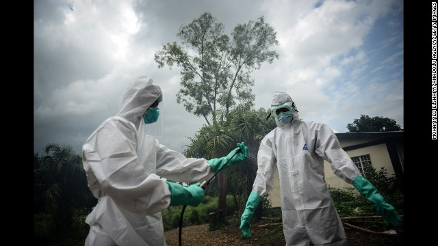 Volunteers working with the bodies of Ebola victims in Kenema, Sierra Leone, sterilize their uniforms on Sunday, August 24. Health officials say the current Ebola outbreak in West Africa is the deadliest ever.