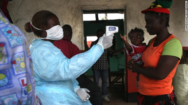 A Liberian health worker checks people for symptoms of Ebola at a checkpoint near the international airport in Dolo Town, Liberia, on August 24.