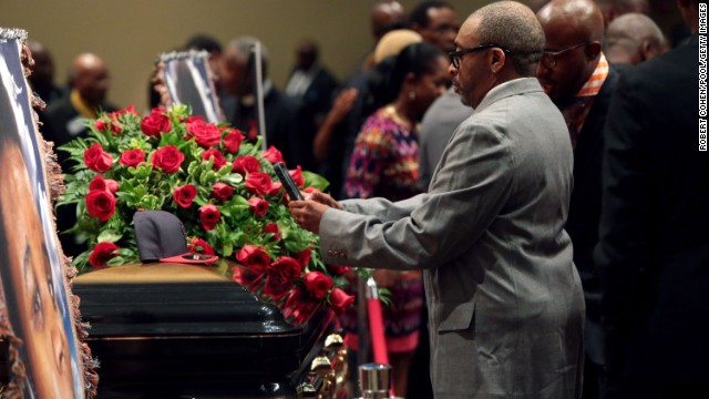 Filmmaker Spike Lee takes a picture of a St. Louis Cardinals baseball cap that rests on top of Brown's casket.
