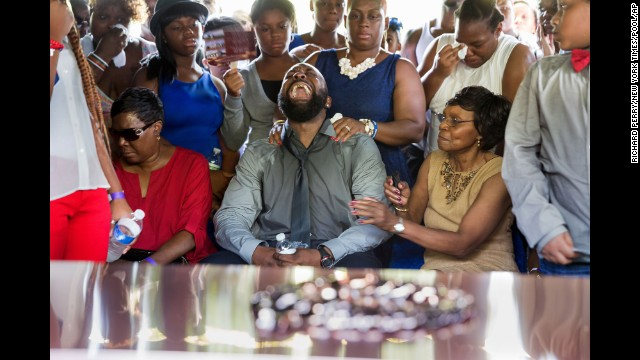 Michael Brown Sr. yells out as the casket holding the body of his son, Michael Brown, is lowered into the ground during his funeral service in St. Louis on August 25.