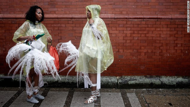AUGUST 26 - LONDON, ENGLAND: Performers in ponchos protect their delicate costumes during the rain soaked Notting Hill Carnival. Over a million visitors attended the two-day event despite the bad weather. The carnival, first organized in 1964, has grown into the largest in Europe.