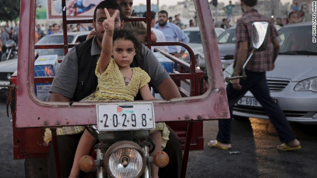 AUGUST 27 - GAZA: A little girl flashes a victory sign as Palestinians in Gaza celebrate the truce with Israel. After more than seven weeks of heavy fighting, <a href='http://edition.preview.cnn.com/2014/08/27/world/meast/mideast-crisis/index.html?hpt=hp_t2'>the two sides have agreed to an open-ended ceasefire</a>.