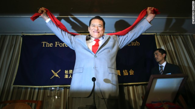 """Inoki poses for photographers at a press conference in Tokyo, August 21. He's organized a two-day wrestling competition in Pyongyang, featuring former NFL player Bob """"The Beast"""" Sapp."""