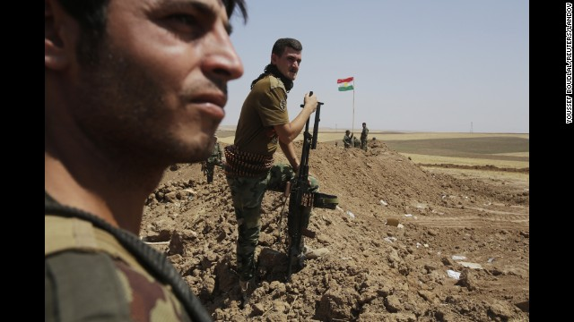 Kurdish Peshmerga forces stand guard at their position in the Omar Khaled village west of Mosul, Iraq, on Sunday, August 24.