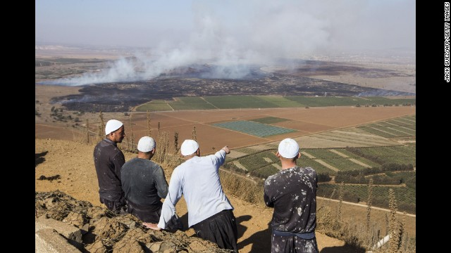 Druze men watch from the Golan Heights side of the Quneitra border with Syria as smoke rises during fighting between forces loyal to Syrian President Bashar al-Assad and rebels on Wednesday, August 27.