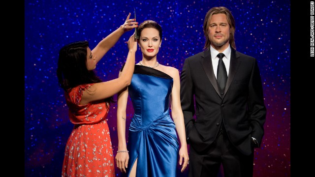 A woman poses with wax figures of Jolie and Pitt at Madame Tussauds in London in December 2013.