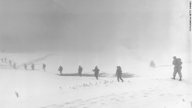 Soldiers of an infantry division move into the mist over a snow-covered field near Krinkelter, Belgium, on December 20, 1944, during the Battle of the Bulge.