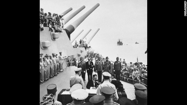 Japanese Foreign Minister Mamoru Shigemitsu signs the Japanese Instrument of Surrender on the deck of the USS Missouri in Tokyo Bay on September 2, 1945, in Japan, officially bringing World War II to an end. Overseeing the surrender is U.S. Gen. Douglas McArthur (right, back to camera).