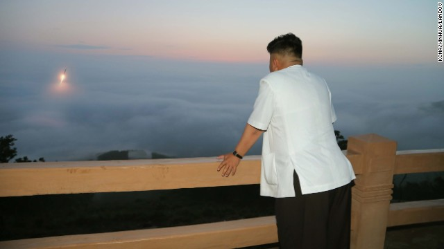 Kim watches a tactical rocket firing drill in June.