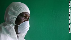 A health worker, wearing a protective suit, conducts an ebola prevention drill at the port in Monrovia on August 29, 2014. The World Health Organization said yesterday that the number of Ebola cases was increasing rapidly and could exceed 20,000 before the virus is brought under control, as the death toll topped 1,500. AFP PHOTO/DOMINIQUE FAGET (Photo credit should read )