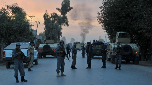 Afghan policemen keep watch after the attack by Taliban militants on the Afghan intelligence service office in Jalalabad.