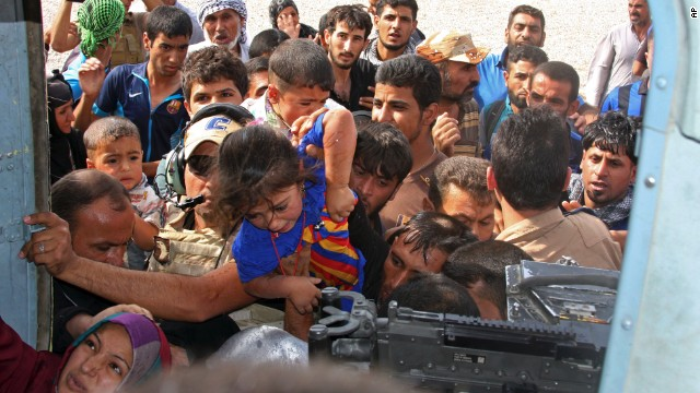 Iraqi Shiite Turkmen, mostly women and children, try to board an Iraqi Army helicopter aid flight bringing supplies to Amerli on Saturday, August 30.