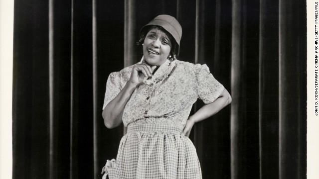 "Considering the early trials Jackie ""Moms"" Mabley had to overcome, her enduring and groundbreaking career in comedy is all the more impressive. After starting off in vaudeville in 1920s New York, she expanded to the silver screen and became the first female comedian to perform at the Apollo Theater. Before Phyllis Diller put on her fright wig and sack dress, Mabley was making audiences double over with her bawdy sense of humor that included frank talk about race. Mabley's talent wasn't widely recognized until the '60s; she passed away in 1975."