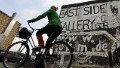 A woman cycles past a portion of the Berlin Wall on October 16, 2008 at the East Side Gallery in Berlin.