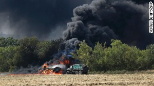 Unmarked military vehicles burn on a country road in Berezove, Ukraine after a clash between Ukrainian troops and pro-Russian separatists.