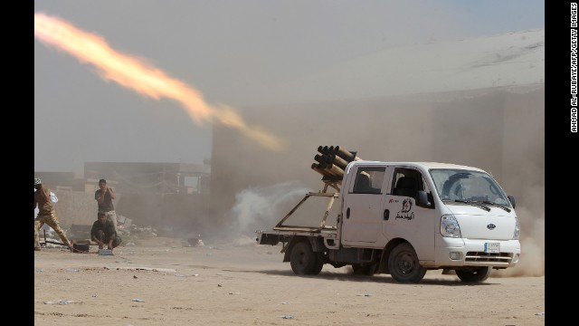 Iraqi Shiite militia fighters fire a rocket toward ISIS positions outside Tikrit, Iraq, on Wednesday, September 3.