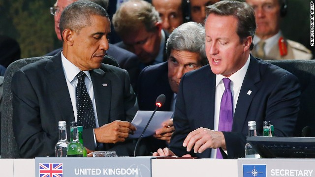 U.S. Secretary of State John Kerry passes a note to Obama as Cameron speaks during a NATO meeting on September 4.