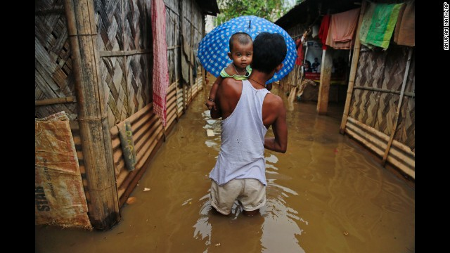 A man carries his son through floodwaters in Gauhati on September 5.
