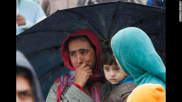 A woman cries as she looks over a flooded road in Srinagar on September 5.