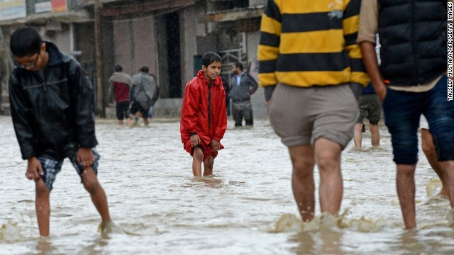 People wade through floodwaters September 5 on the outskirts of Srinagar.