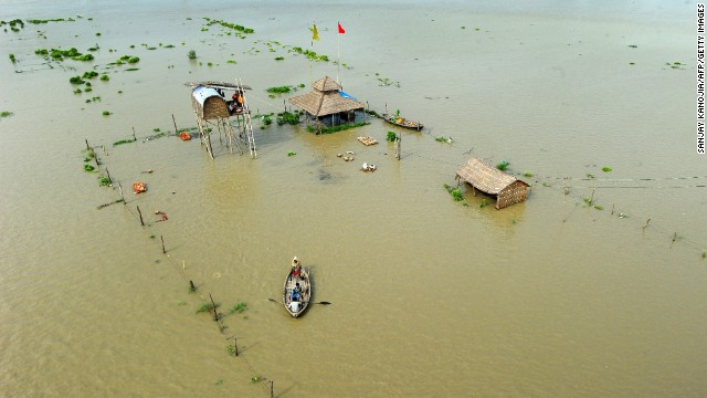 People flee submerged huts on the flooded banks of the Ganga river in Allahabad on Friday, August 8.