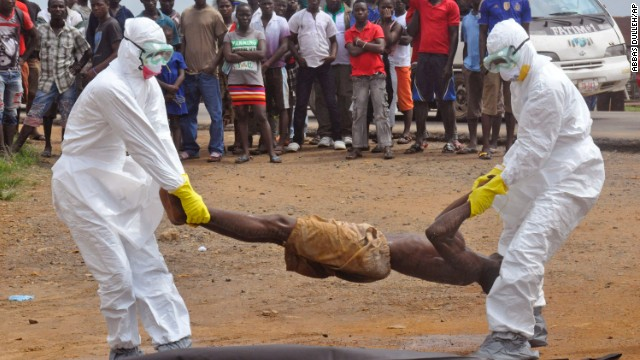Health workers in Monrovia place a corpse into a body bag on September 4.