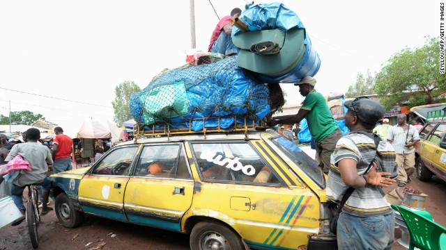 After an Ebola case was confirmed in Senegal, people load cars with household items as they prepare to cross into Guinea from the border town of Diaobe, Senegal, on Wednesday, September 3.