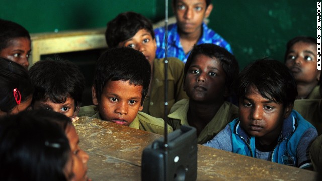SEPTEMBER 5 - ALLAHABAD, INDIA: Schoolchildren crowd around a radio as they listen to a broadcast by Indian Prime Minister Narendra Modi delivering his Teachers' Day speech at a primary municipal school at Bakshi Kala Daraganj. Modi addressed hundreds of thousands of students during a live telecast to classrooms across India.