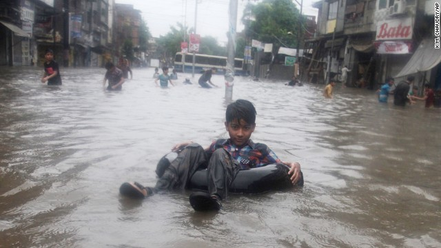 Pakistani children play in a road flooded after heavy rain in Lahore, Pakistan, on Friday, September 5.