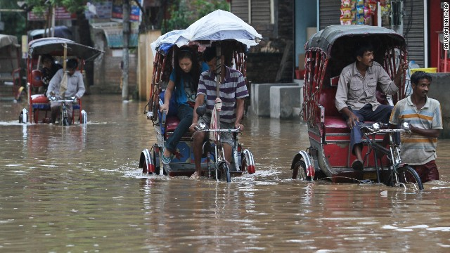 Rickshaw drivers transport commuters through floodwaters on September 5 in Gauhati, India.