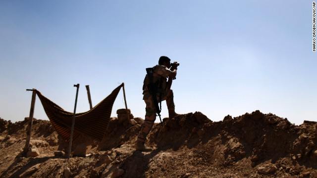 A Kurdish fighter eyes ISIS positions outside Makhmour, Iraq, on Saturday, September 6.