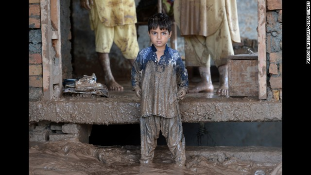 A child waits for his family to clean their home after flooding in Rawalpindi, Pakistan, on September 6.