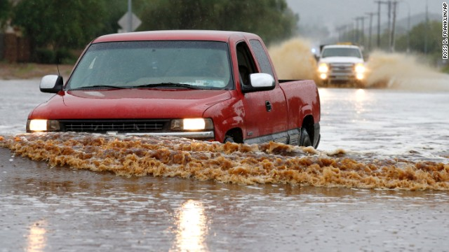 People attempt to drive their vehicles through severely flooded streets in Phoenix on September 8.