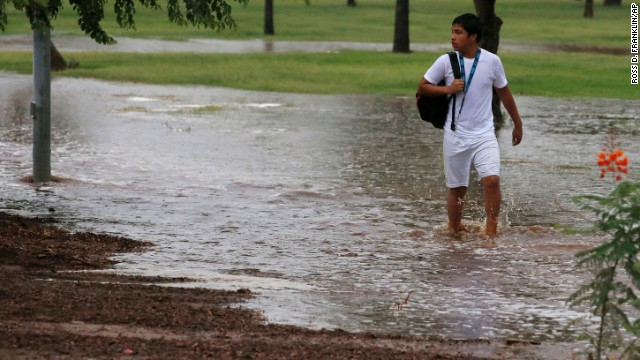A student tries to walk along a flooded sidewalk so he can be picked up by his parents September 8 in Phoenix.
