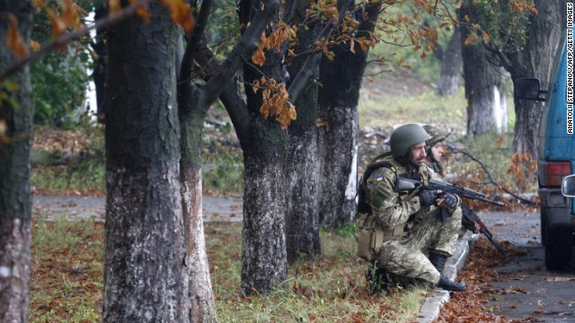 Ukrainian troops protect themselves from a nearby shooting in Debaltseve, Ukraine, on Tuesday, September 9.