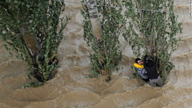 People in Srinagar hang onto a tree to prevent being swept away by floodwaters on September 9.