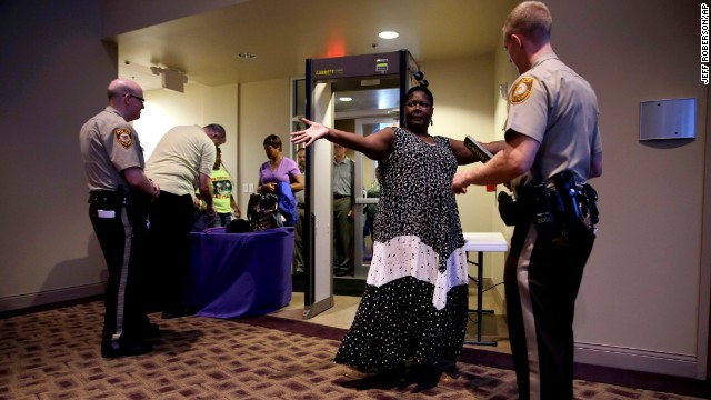 Patricia Cowan holds out her arms for a St. Louis County police officer as she and others are searched as they enter Greater Grace Church before the start of the meeting.