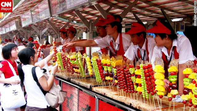 Skewers of sweet pineapple, tart green grapes, and other colorful arrangements of fruit line a concession stand in<a href='http://ireport.cnn.com/docs/DOC-1156894'> Beijing, China</a>.