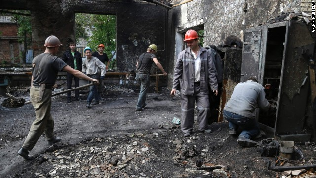 Workers clear rubble Thursday, September 11, after the bombing of a mine in Donetsk, Ukraine. A fledgling truce between the Ukrainian government and pro-Russian rebels is already under threat, as both sides have accused the other of violating it.