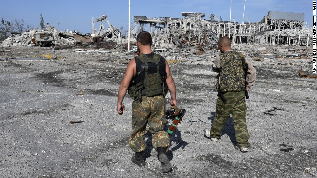 Armed pro-Russian rebels walk September 11 in front of the destroyed Luhansk International Airport in Luhansk, Ukraine. The rebels took control of the airport on September 1 after heavy fighting with the Ukrainian army.
